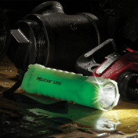 The body of the Pelican 3325 LED torch glowing green on the fatory floor